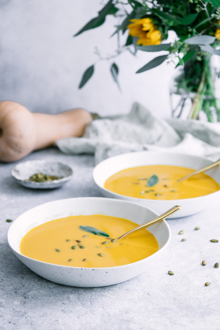 Two white bowls with yellow butternut squash soup and a bouquet of flowers.