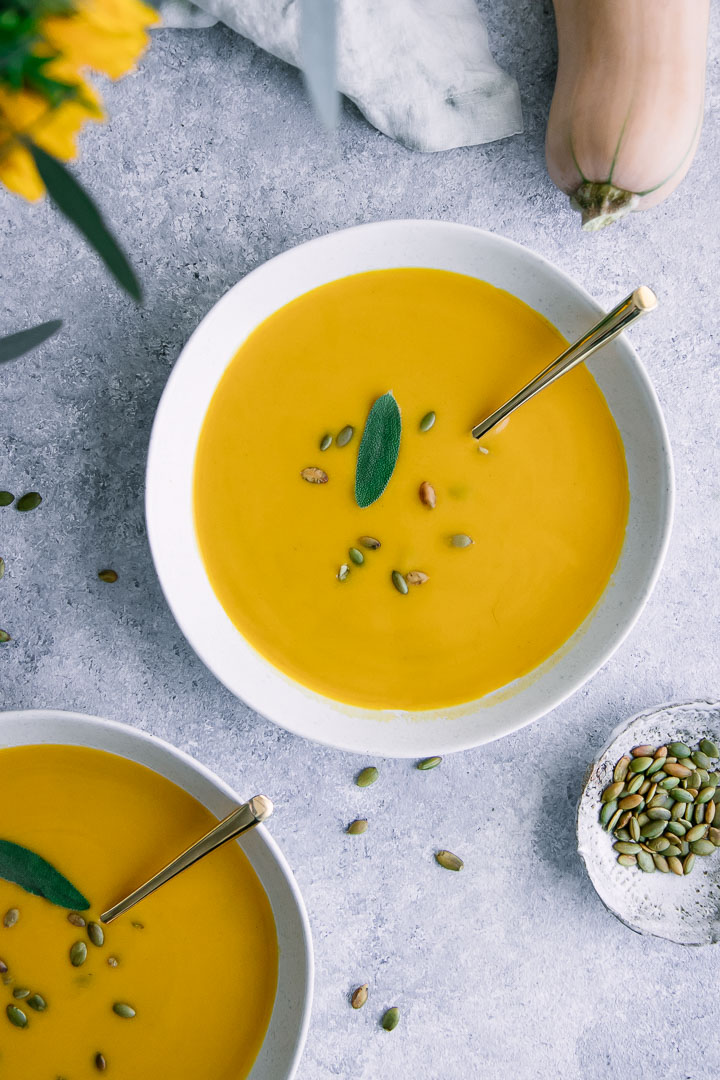 A white bowl with yellow vegan butternut squash soup with a sage leave for garnish.