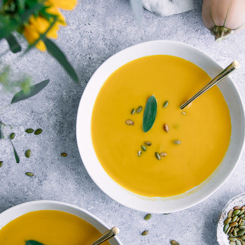 A bowl of yellow butternut squash soup on a blue table with pumpkin seeds.