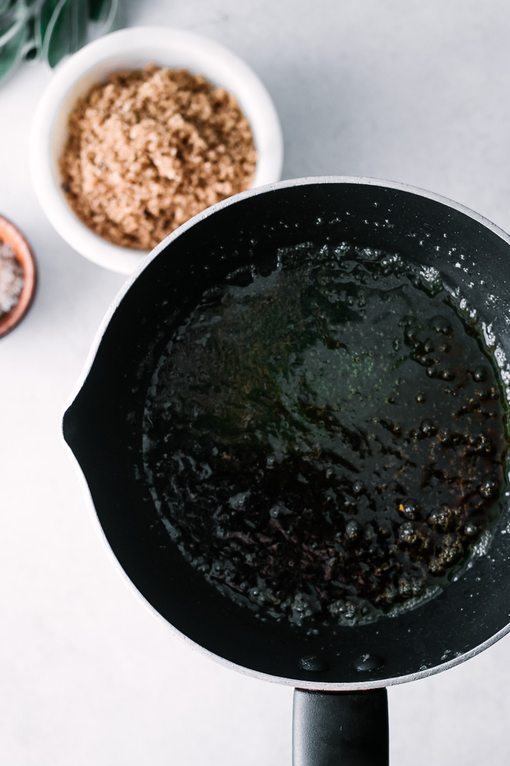 A sauce pan with brown sugar, sage, and maple syrup