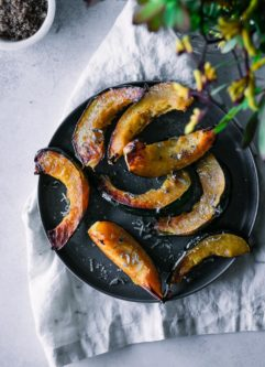 roasted acorn squash pieces on a dark plate with a white napkin