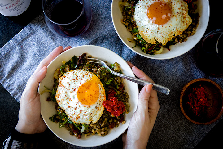 Two easy lentil bowls with a sunny egg on each and two hands holding a fork.