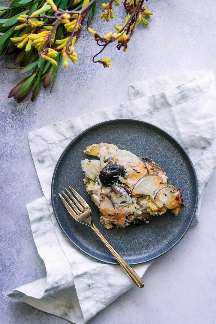 Scalloped potatoes with leeks and mushrooms on a blue plate on a blue table with yellow flowers.