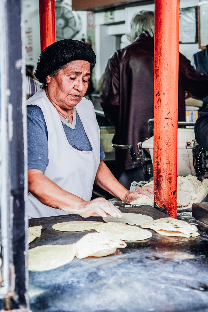 A woman making tortillas on the streets of Mexico city food tour.