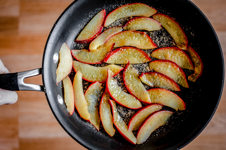 Sliced pluots cooking in a black pan.