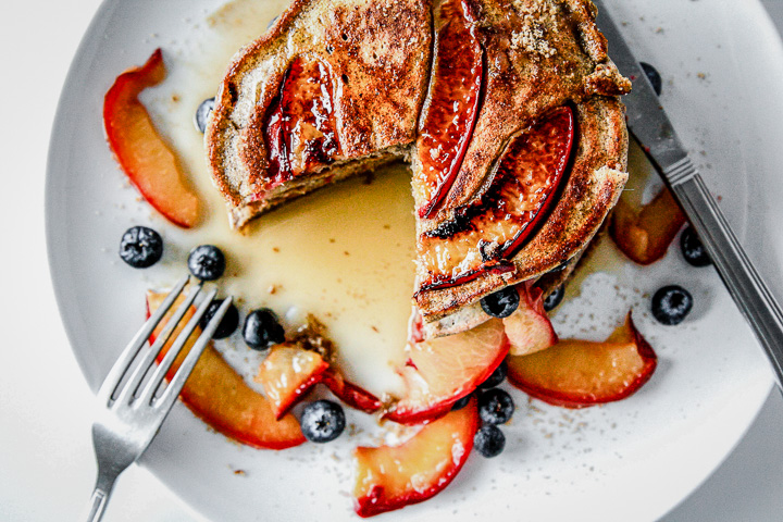 Pluot brown sugar buckwheat pancakes on a white plate being cut with a fork.