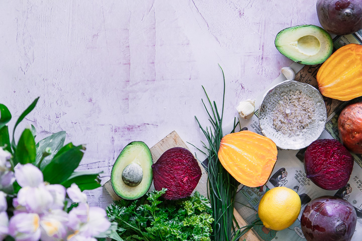 Beets, avocados, lemons, and herbs on a pink table