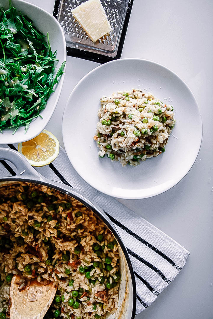 Mushroom pea risotto with white truffle oil on a white plate on a white table with a side salad and a slice of lemon.
