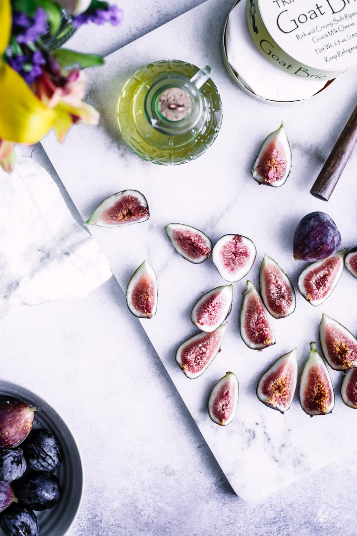 Sliced figs on a cutting board with a bottle of maple syrup.