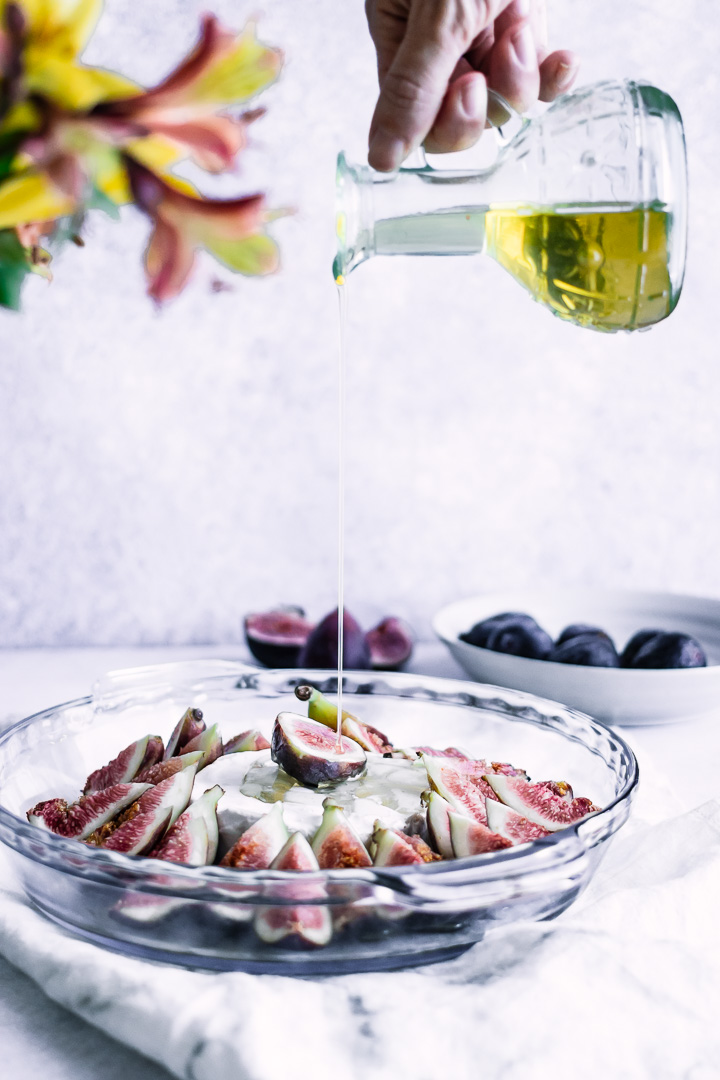 A hand drizzling maple syrup over a glass baking dish with figs and brie.