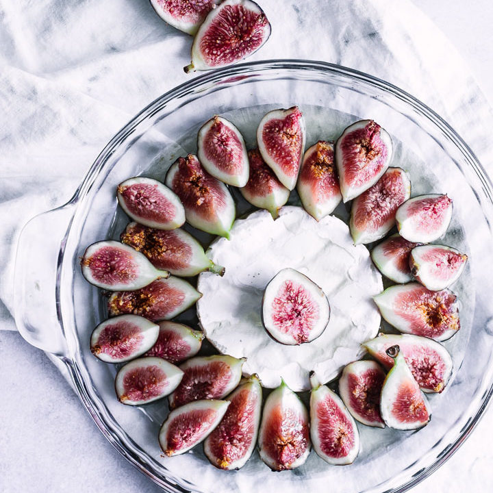 A glass baking dish with figs, brie, and maple syrup.