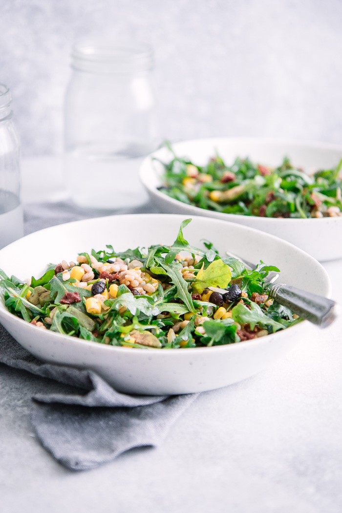 A farro and arugula salad in two bowls on a white table.