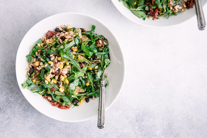 A simple vegan salad with grains, greens, and sun dried tomatoes in two white bowls on a blue table.
