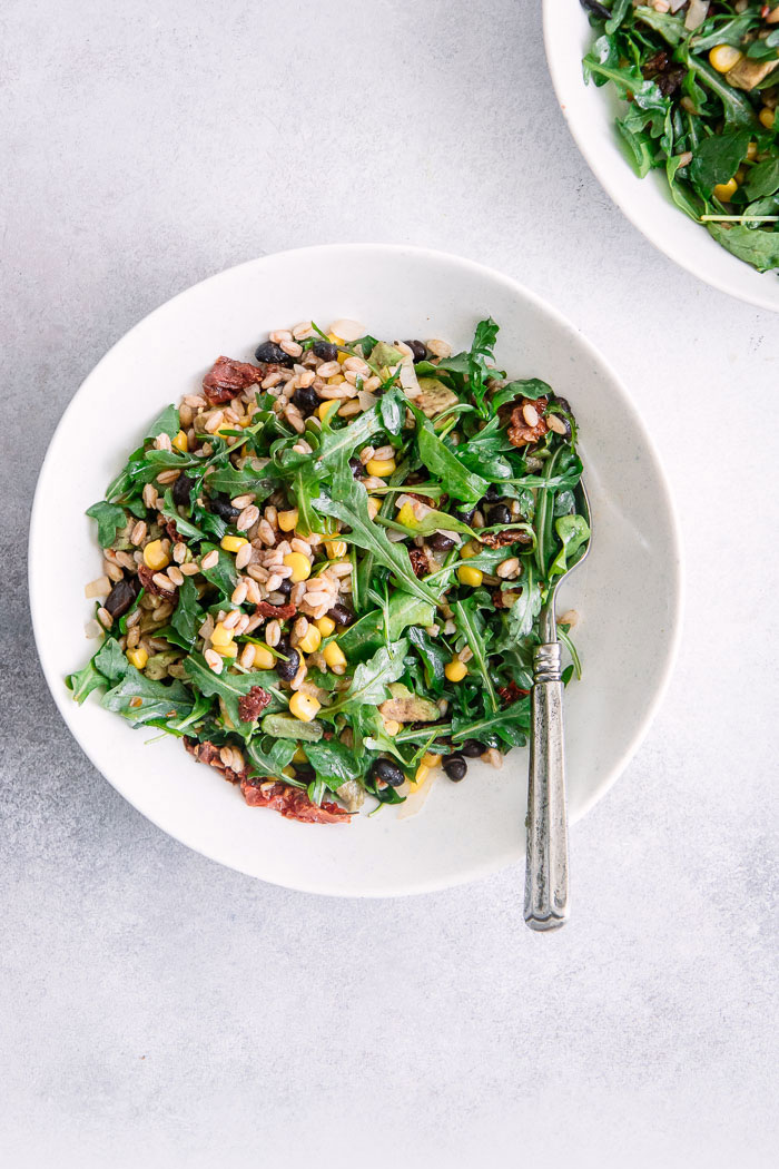 A grain and greens salad in a while bowl on a blue table with a silver fork.