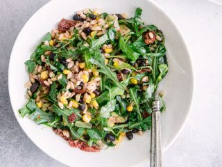 "A green and grains salad with two white bowls with the words ""black bean corn farro salad"" in black and red writing."