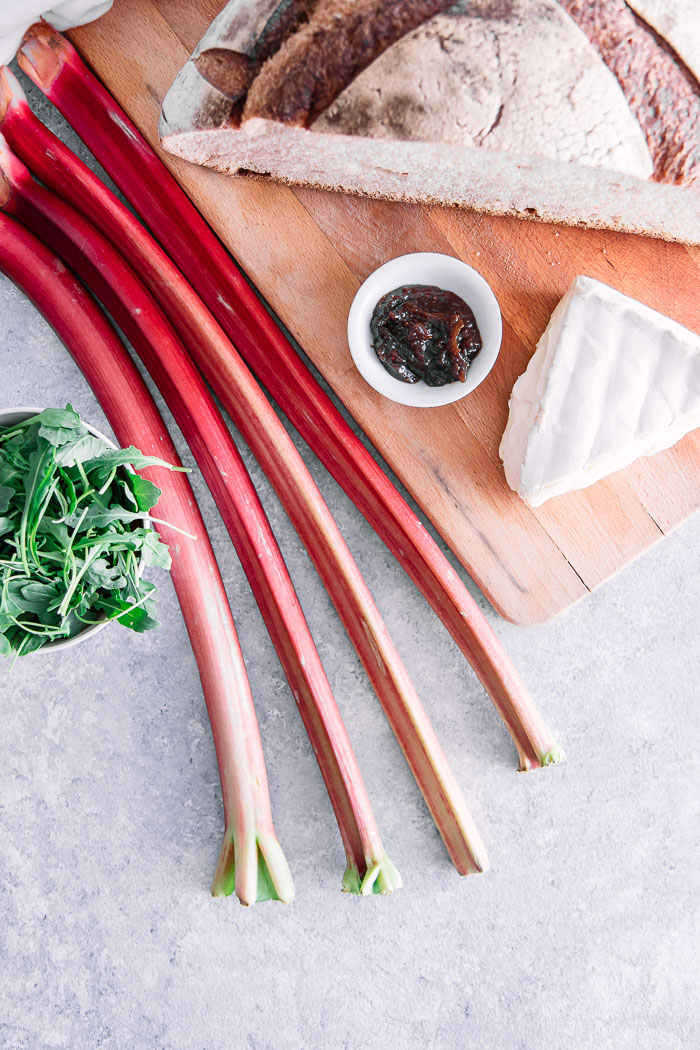 Rhubarb, brie, arugula, jam, and bread on a wooden cutting board.