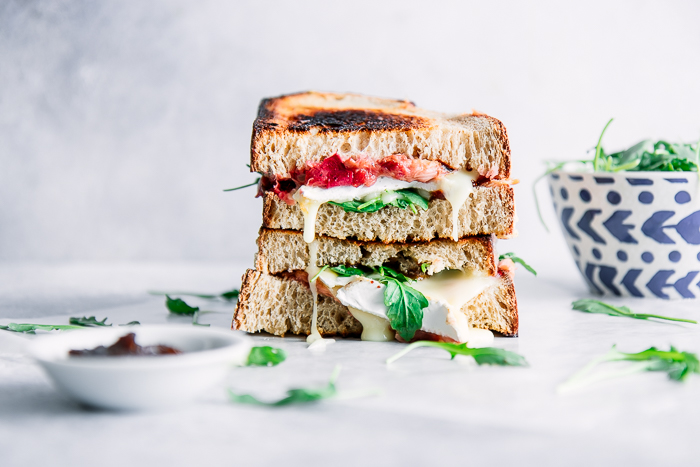 A stacked sandwich with brie and rhubarb on a white table and gooey cheese.