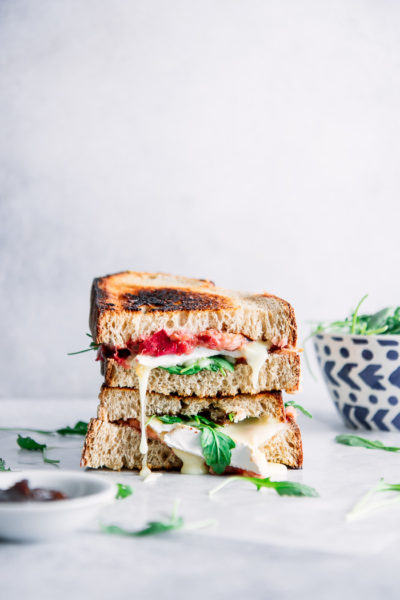 A stacked sandwich with rhubarb, argula, and brie on a white table with jam and a blue bowl.