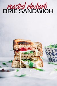 """A cut sandwich stacked on top of one another with melted brie cheese, arugula, and whole grain bread and the words """"roasted rhubarb brie sandwich"""" in black letters."""