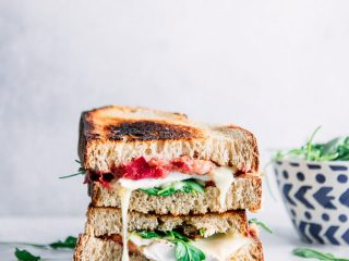 "A cut sandwich stacked on top of one another with melted brie cheese, arugula, and whole grain bread and the words ""roasted rhubarb brie sandwich"" in black letters."