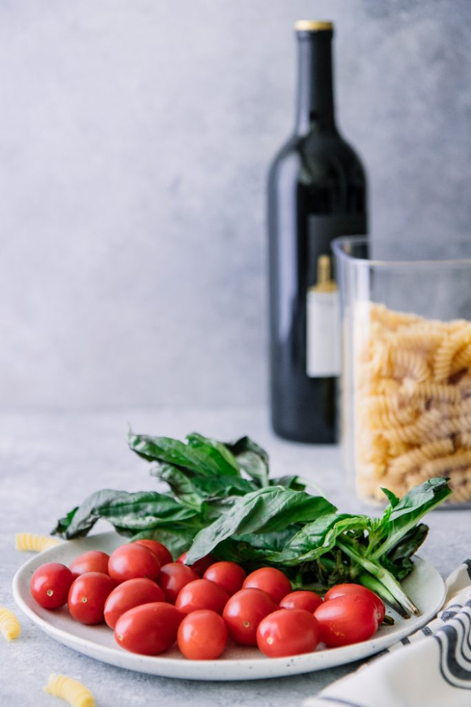 A white plate with cherry tomatoes and basil on a blue table with a jar of fusilli pasta and a bottle of wine in the background.