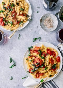 Two white plates of pasta salad with tomatoes, basil, and fusilli pasta on a blue table with a glass of wine.