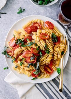 A white plate with Italian cold pasta salad with fusilli pasta, tomatoes, and basil with a gold fork.