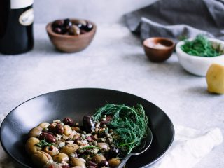 "A black bowl with mixed olives and herbs with a bottle of wine and small bowls in the background with the words ""warm marinated olives."""