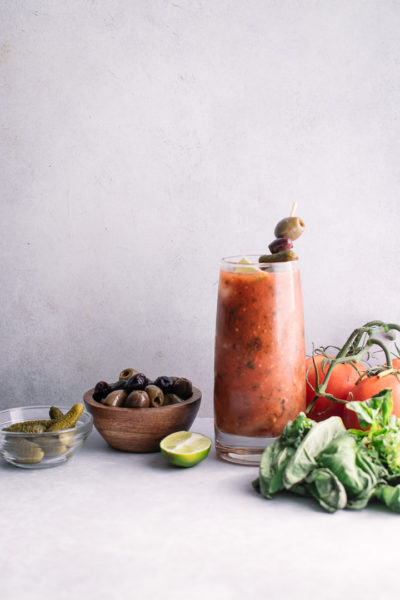 A tall glass of homemade spicy bloody mary mix with pickles, olives, and herbs.