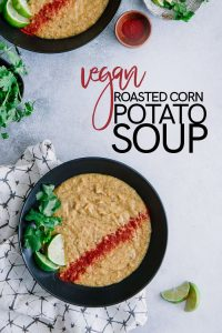 "Vegan corn and potato soup in a black bowl with red paprika, green cilantro and limes, and a white and black patterned napkin with the words ""vegan roasted corn potato soup"" in black and red writing."