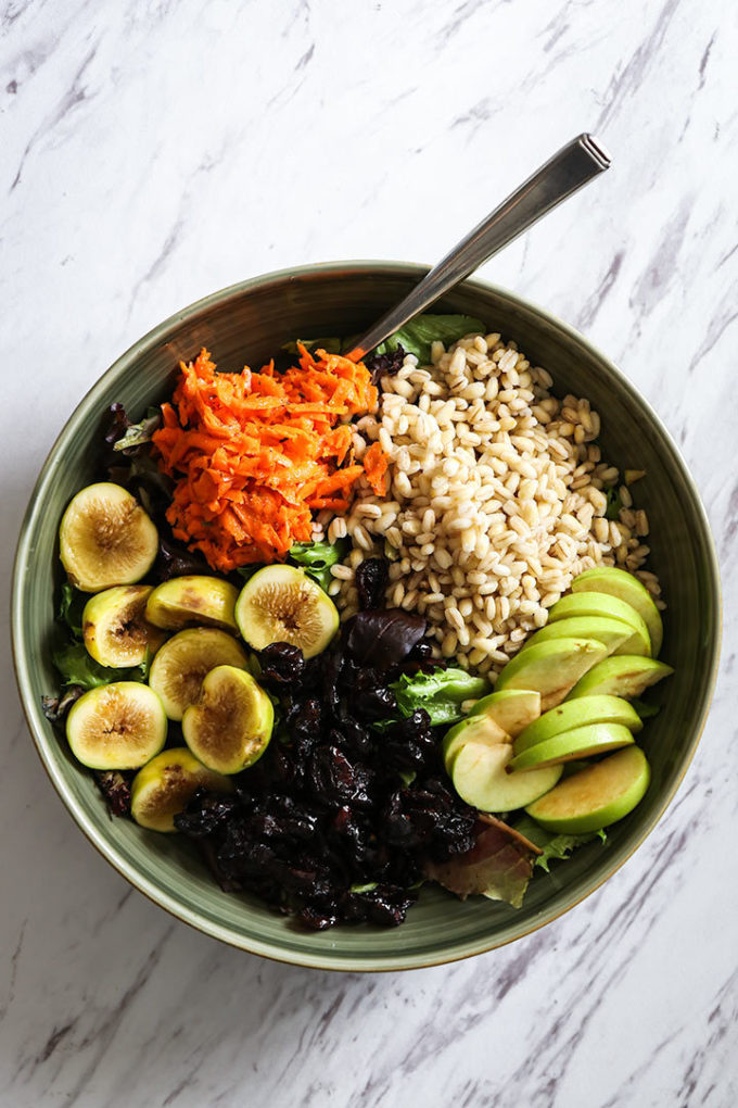 a fall grain bowl with warm barley, apples, figs, cranberries, carrots, and maple dressing in a green bowl on a white table
