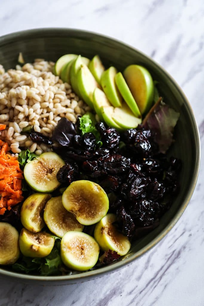 a green bowl filled with grains, sliced apples, sliced figs, dried cranberries, and shredded carrots on a white table