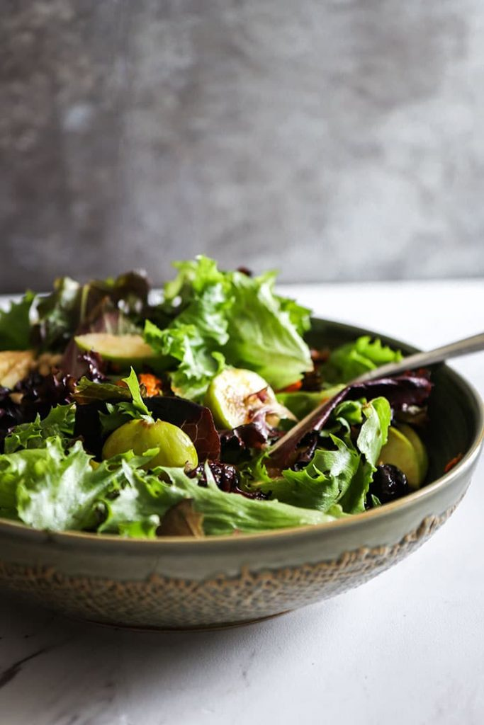 a large salad bowl with leafy greens, grains, and fall produce on a white table