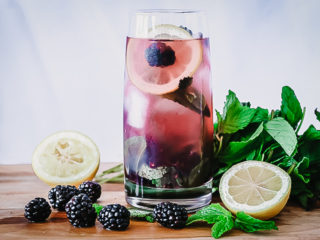 A glass of boozy blackberry lemonade on a cutting board with fresh fruit.