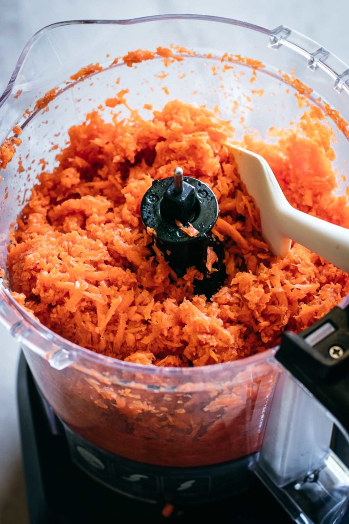 Shredded carrots and a spoon in a food processor