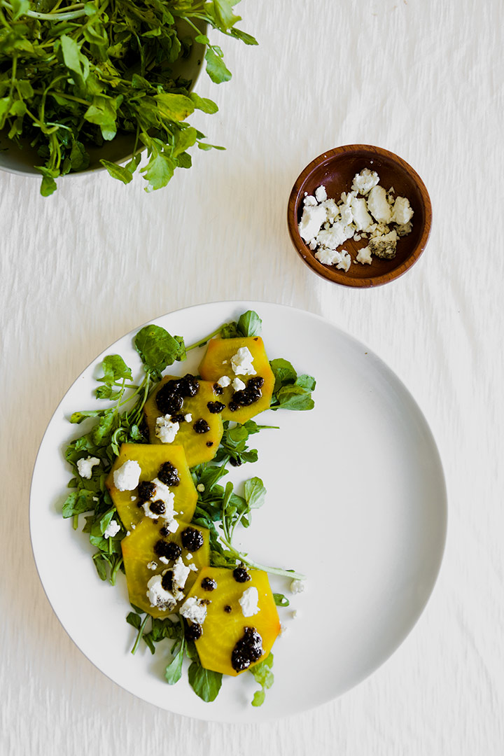 roasted golden beet carpaccio on a white place with a white table.
