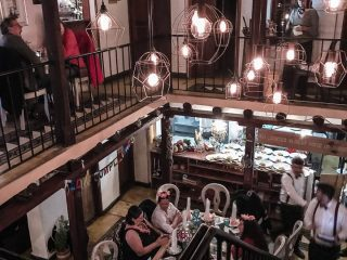 A two story restaurant with diners sitting at tables.