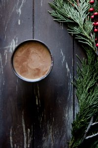 a mocha latte cup on a wood table with green and red holly branches