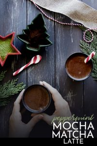 """hands holding a mocha latte on a wood table with the words """"peppermint mocha matcha latte"""" in white letters"""