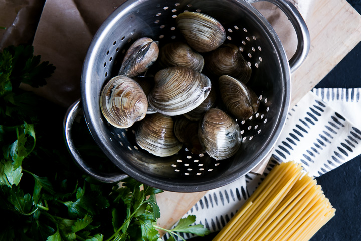 clams in a colander with parsley and spaghetti pasta noodles