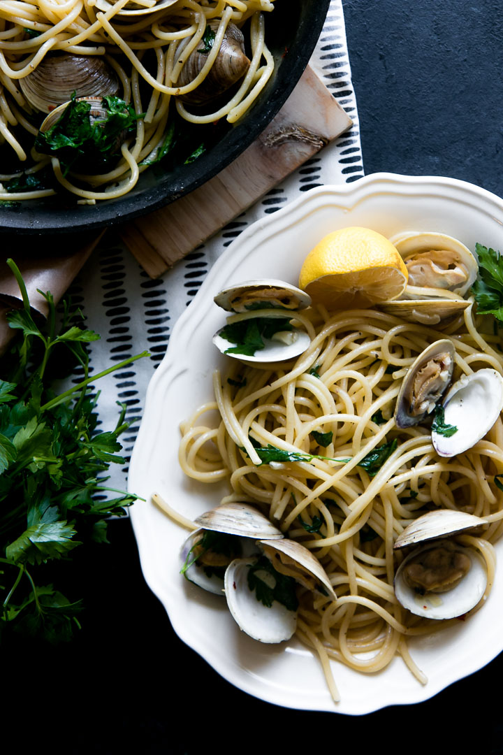 Pasta with clams on a white plate on a black table.