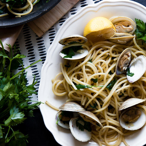 a plate of pasta with clams (pasta con vongole) with fresh parsley