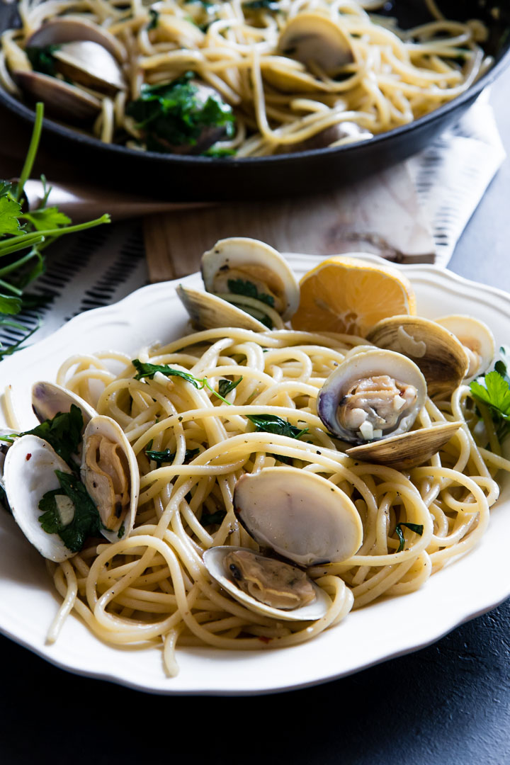 bucatini with clams, white wine, and parsley on a black table