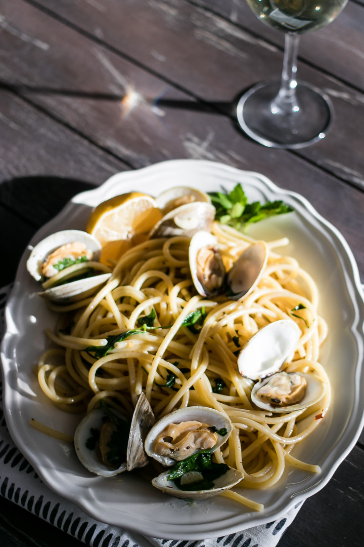 a plate of pasta with clams with a glass of white wine on a wood table