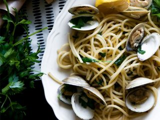 a plate of bucatini pasta with clams, lemons, and parsley on a white plate
