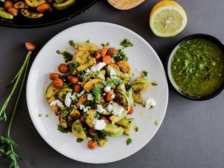 Carrots and squash on a white plate topped with carrot top pesto and goat cheese.