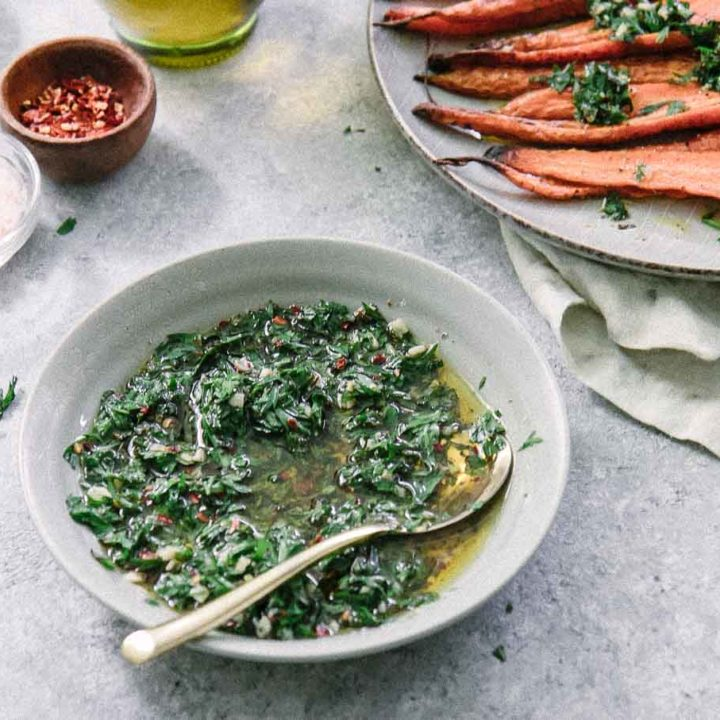 a bowl of green chimichurri sauce with carrot leaves in a blue bowl and a gold spoon