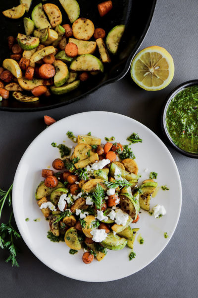 Carrots and squash on a white plate topped with carrot top chimichurri and goat cheese.