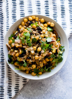 za'atar crispy chickpea and leek salad in a white bowl on a blue table with a white napkin