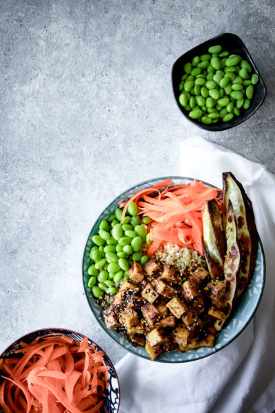 Ginger Soy Tofu Bowl recipe in a blue bowl on a grey table with a bowl of edamame and a bowl of shaved carrots.